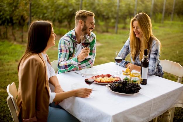 Jóvenes junto a la mesa en el viñedo