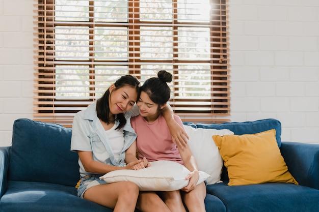 Jóvenes lesbianas lgbtq mujeres asiáticas pareja abrazan y besan en casa