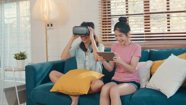 Jóvenes lesbianas lgbtq mujeres asiáticas pareja usando tableta en casa