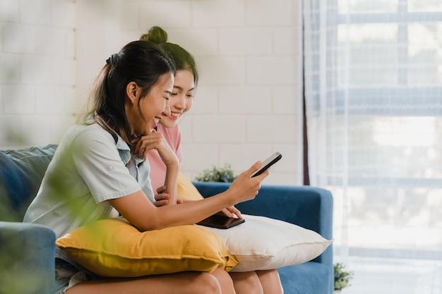 Jóvenes lesbianas lgbtq mujeres pareja usando el teléfono móvil en casa