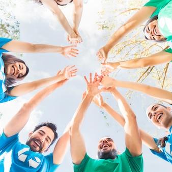 Jóvenes levantando las manos al cielo en círculo