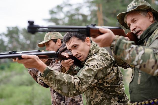 Jóvenes y mayores cazadores francotiradores con el objetivo de apuntar.