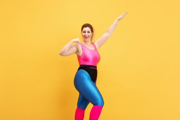 Jóvenes modelos femeninos caucásicos de talla grande entrenando en amarillo