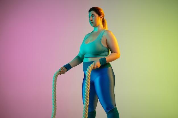Jóvenes modelos femeninos caucásicos de talla grande entrenando en pared verde púrpura degradado