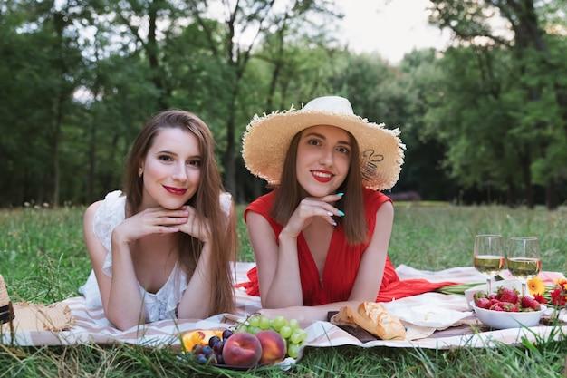 Jóvenes muchachas atractivas en un picnic en un parque de la ciudad.