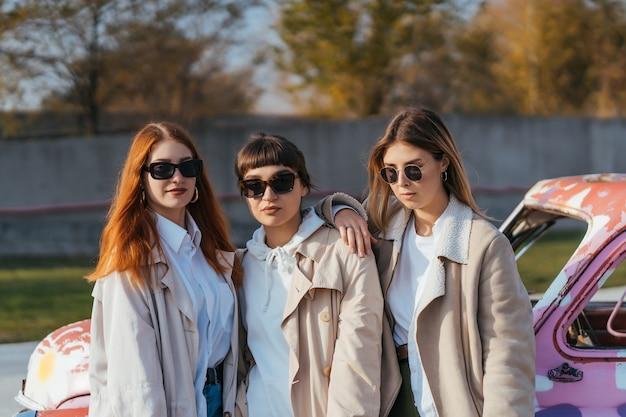 Jóvenes mujeres felices con bolsas de compras posando cerca de un viejo coche decorado