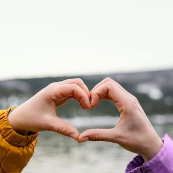 Jóvenes mujeres hermosas en la naturaleza haciendo forma de mano de corazón