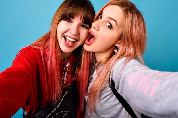 Jóvenes mujeres locas hipster haciendo selfie en pared azul, emociones divertidas sorprendidas, largos pelos rosados, atuendos casuales.