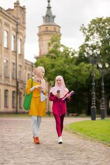 Jóvenes mujeres musulmanas. jóvenes mujeres musulmanas con ropa brillante caminando juntos a la universidad