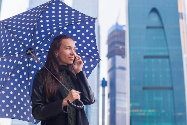 Jóvenes mujeres de negocios encantadoras hablando por teléfono bajo una sombrilla en un día lluvioso
