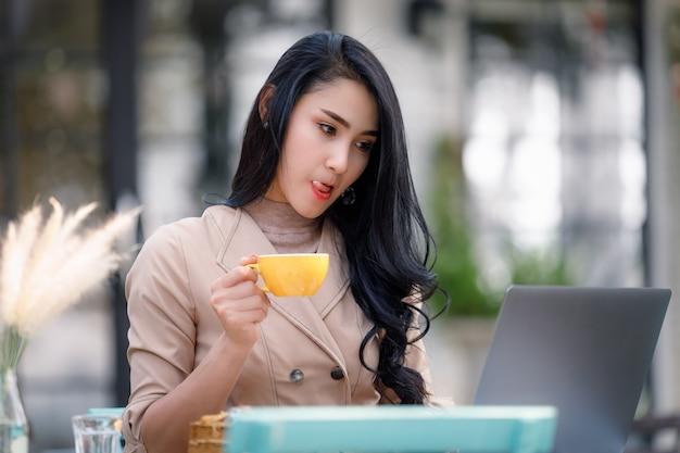 Jóvenes mujeres de negocios independientes sentado mesa de madera en el jardín y relajarse tomando café