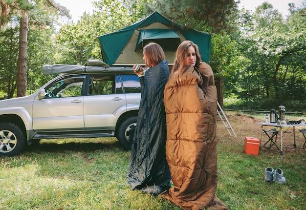 Jóvenes mujeres soñolientas que se despiertan dentro de los sacos de dormir en una fría mañana en el camping