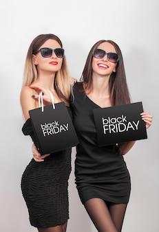 Jóvenes mujeres sonrientes mostrando bolsa de compras en viernes negro de vacaciones.