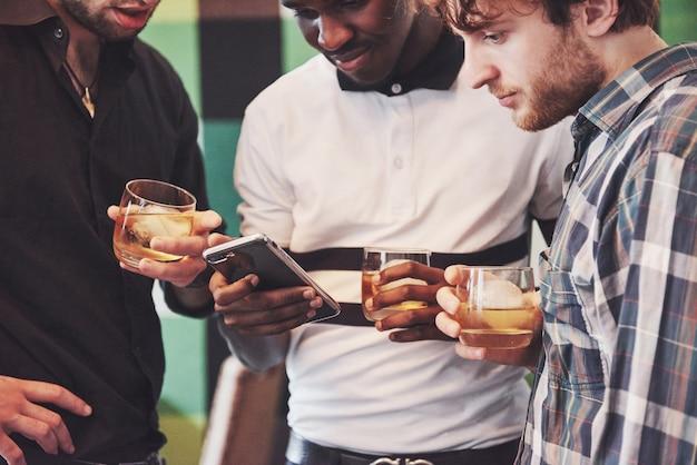 Jóvenes multiétnicos celebrando y bebiendo tostadas de whisky