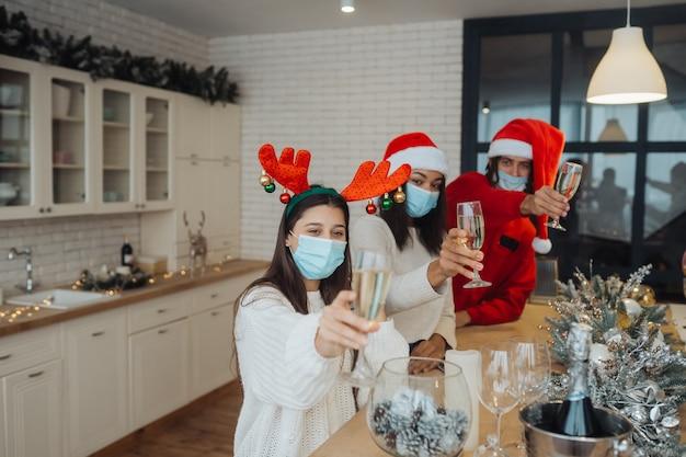 Jóvenes multiétnicos celebrando la víspera de año nuevo tintineando vasos brindando, amigos multirraciales divirtiéndose en la celebración de la fiesta, felicitando bebiendo champán