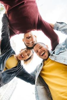Jóvenes multirraciales amigos riendo y de pie en círculo