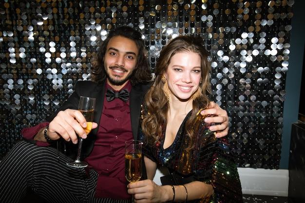 Jóvenes novios cariñosos con flautas de champán animando en la fiesta en el club nocturno frente a la cámara