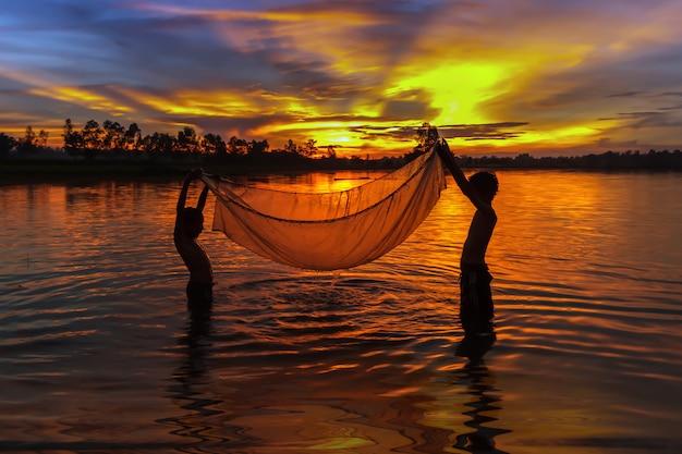 Jóvenes pescadores tailandeses buscando peces en la puesta de sol.