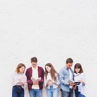 Jóvenes de pie y leyendo libros discutiendo contenido