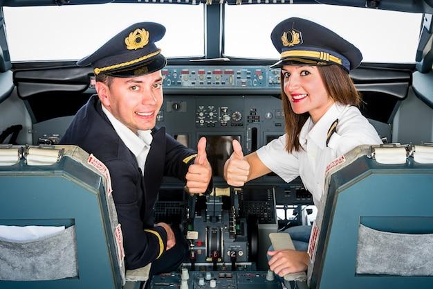 Jóvenes pilotos estudiantes posando con los pulgares hacia arriba en el simulador de vuelo