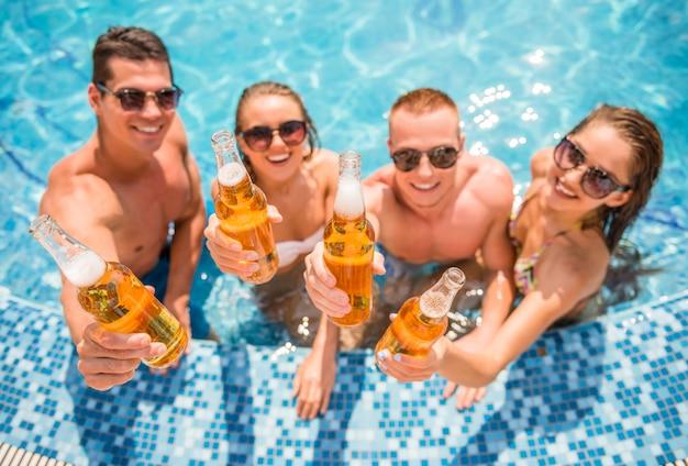 Jóvenes en piscina, sonriendo y bebiendo cerveza.
