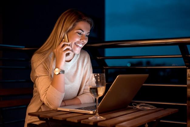 Los jóvenes ponen en marcha un pequeño empresario hablando con un cliente por teléfono móvil en su casa. imagen de alta iso.