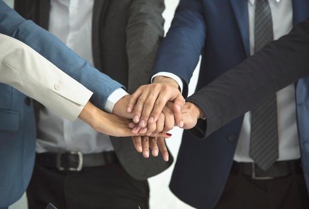 Jóvenes poniendo sus manos juntas. concepto de trabajo en equipo y unidad.