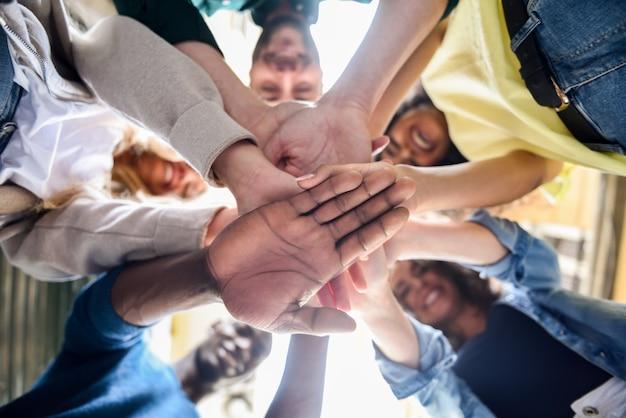 Jóvenes poniendo sus manos juntas.