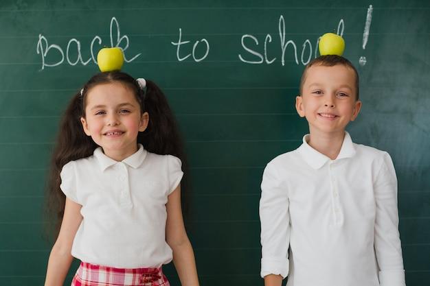 Jóvenes posando con manzanas en el aula