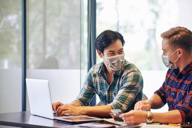 Jóvenes positivos con máscaras médicas sentados en la mesa de la oficina y discutiendo la forma de desarrollo empresarial en línea