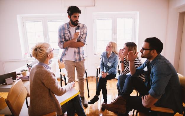 Jóvenes con problemas para escuchar la confesión de su amigo nervioso mientras están sentados juntos en una terapia grupal especial.