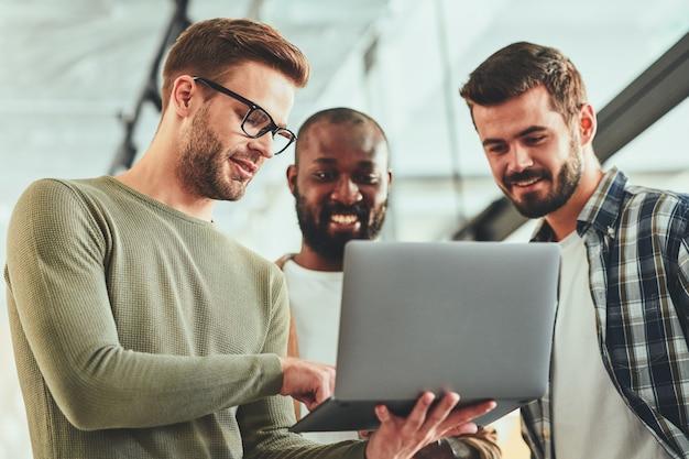 Jóvenes profesionales masculinos viendo algo en la pantalla del portátil