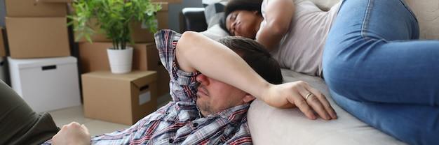 Jóvenes propietarios descansando en el sofá y el piso
