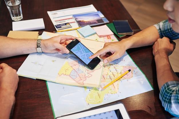 Los jóvenes que planean un viaje, están revisando mapas en papel y aplicaciones en línea en el teléfono inteligente