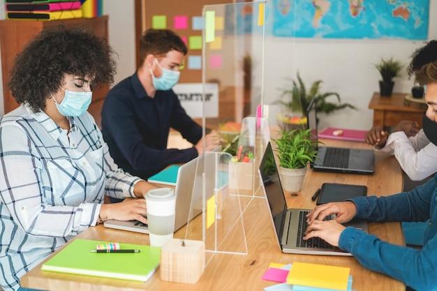 Jóvenes que trabajan dentro de la oficina de coworking con máscaras protectoras para la prevención de la propagación del coronavirus