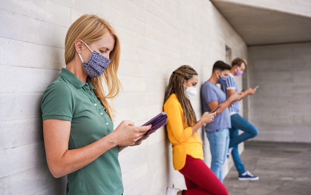 Jóvenes que usan máscaras de seguridad para la cara usando teléfonos móviles inteligentes mientras mantienen la distancia social