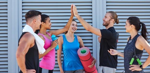 Jóvenes de raza mixta feliz dando cinco alto cerca de la pared en la calle