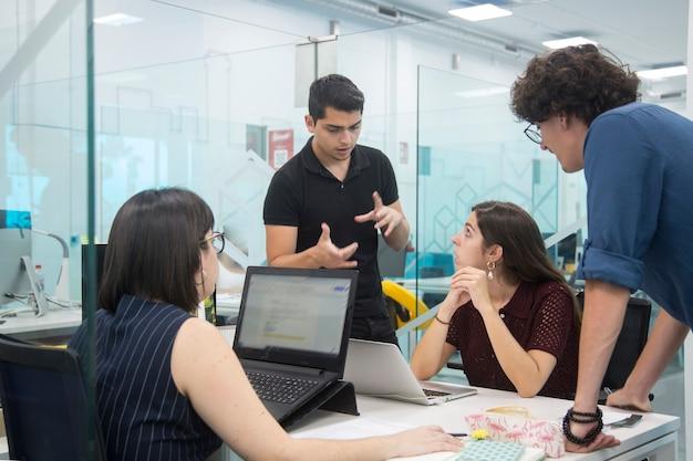 Jóvenes reunidos en un coworking discutiendo una nueva campaña de marketing.