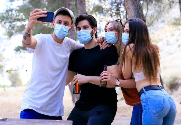Jóvenes reunidos después de la cuarentena causada por el covid19. tome precauciones con máscaras quirúrgicas y tome fotos junto con un teléfono inteligente.