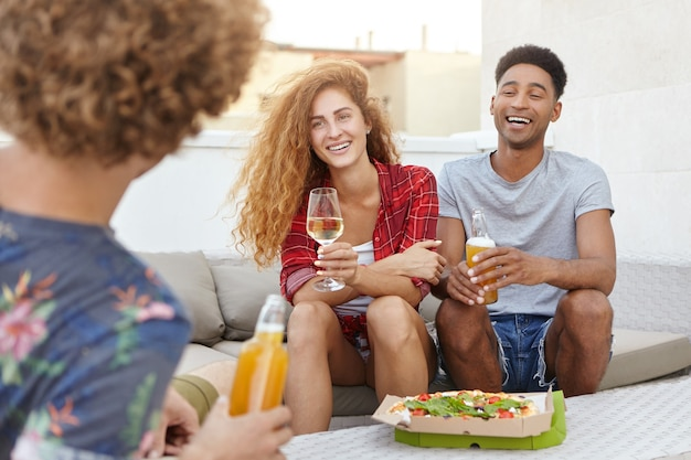 Jóvenes reunidos juntos sentados en un cómodo sofá teniendo una conversación interesante