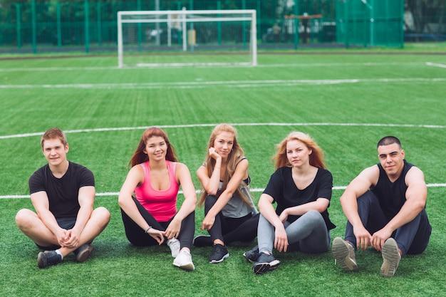 Los jóvenes se sientan en la hierba en el campo de fútbol.