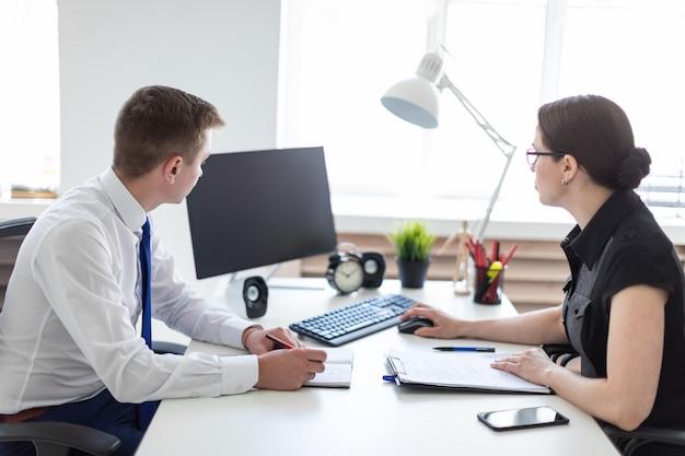 Los jóvenes se sientan en la oficina a la mesa de la computadora y trabajan con documentos.