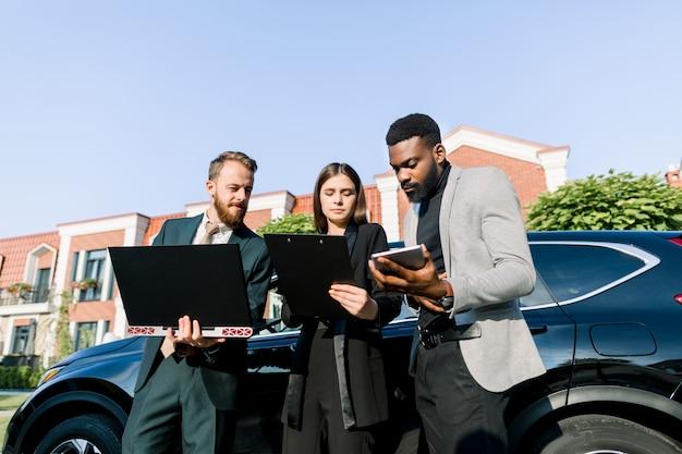 Los jóvenes socios comerciales de confianza, el hombre africano y el hombre y la mujer de raza blanca, están trabajando juntos usando una tableta y una computadora portátil antes de un viaje de negocios de pie cerca del automóvil negro al aire libre.