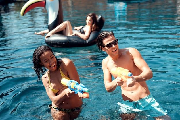 Jóvenes sonrientes amigos divirtiéndose en la piscina