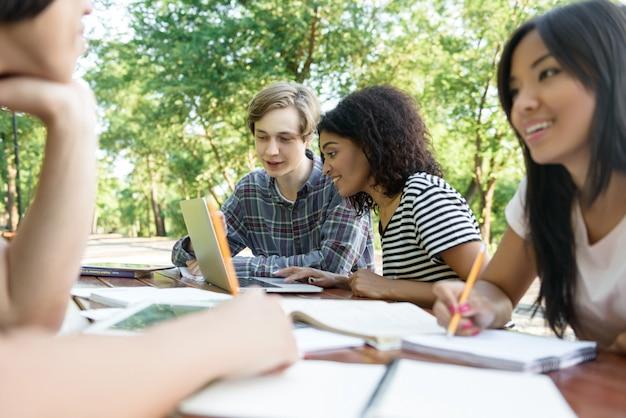 Jóvenes sonrientes estudiantes sentados y estudiando al aire libre