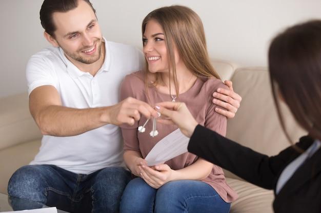 Jóvenes sonrientes propietarios de pareja consiguiendo llaves para poseer apartamento de casa