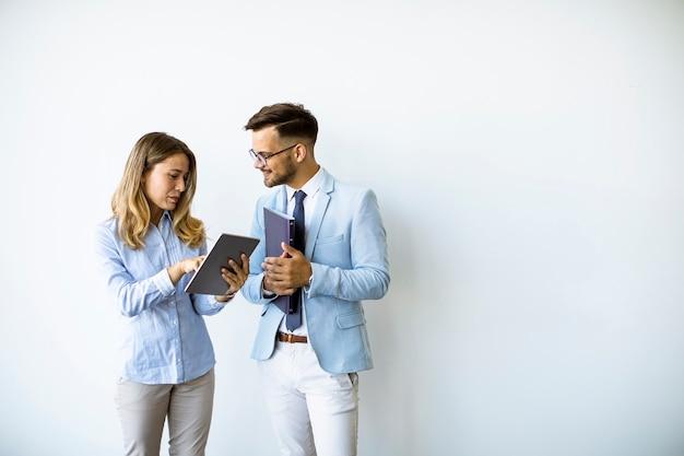 Jóvenes con tableta digital junto a la pared de la oficina