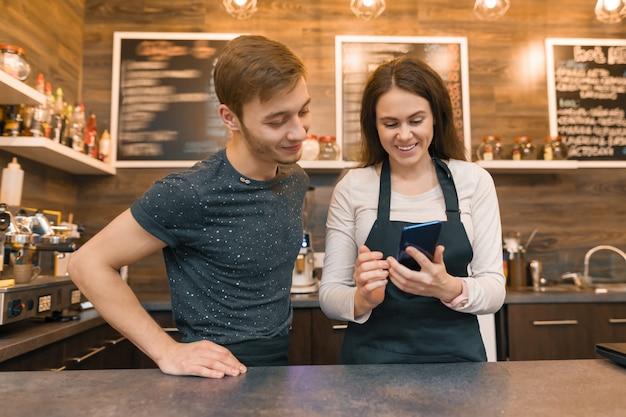 Jóvenes trabajadores de cafetería hombre y mujer detrás de la barra del bar, hablando mirando en el teléfono inteligente