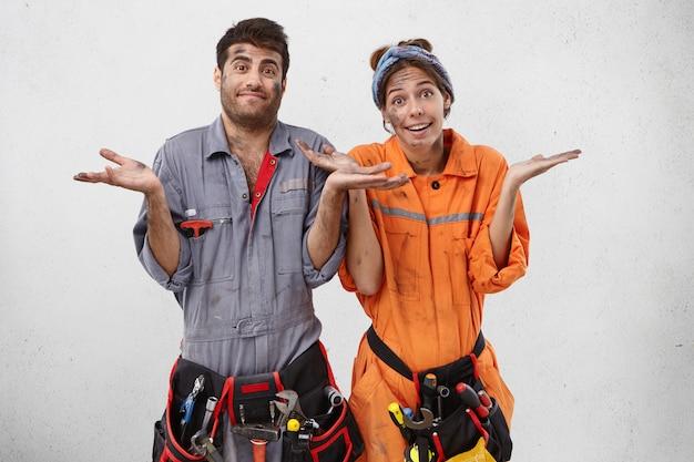 Jóvenes trabajadores de la construcción desordenados que trabajan duro se encogen de hombros con desconcierto
