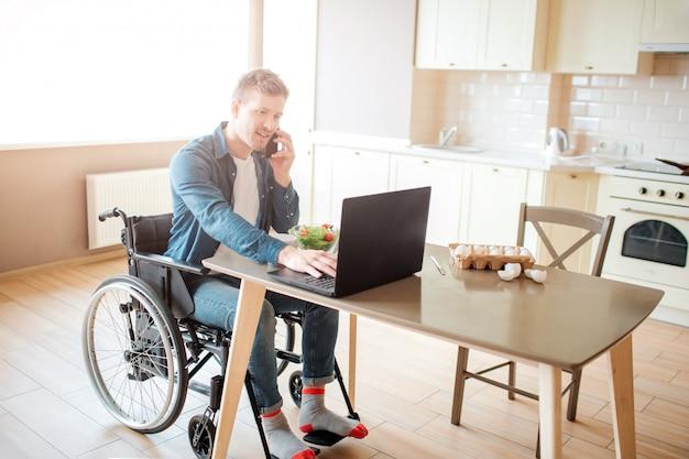 Los jóvenes trabajadores con discapacidad y necesidades especiales se sientan a la mesa y trabajan. él usa la computadora portátil y habla por teléfono. solo en la cocina. grave y concentrado.